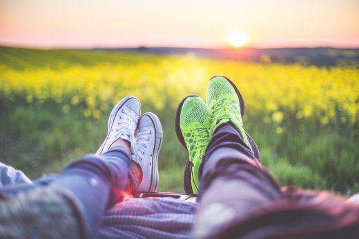 2 jeunes couchés dans l'herbe pour regarder un coucher de soleil