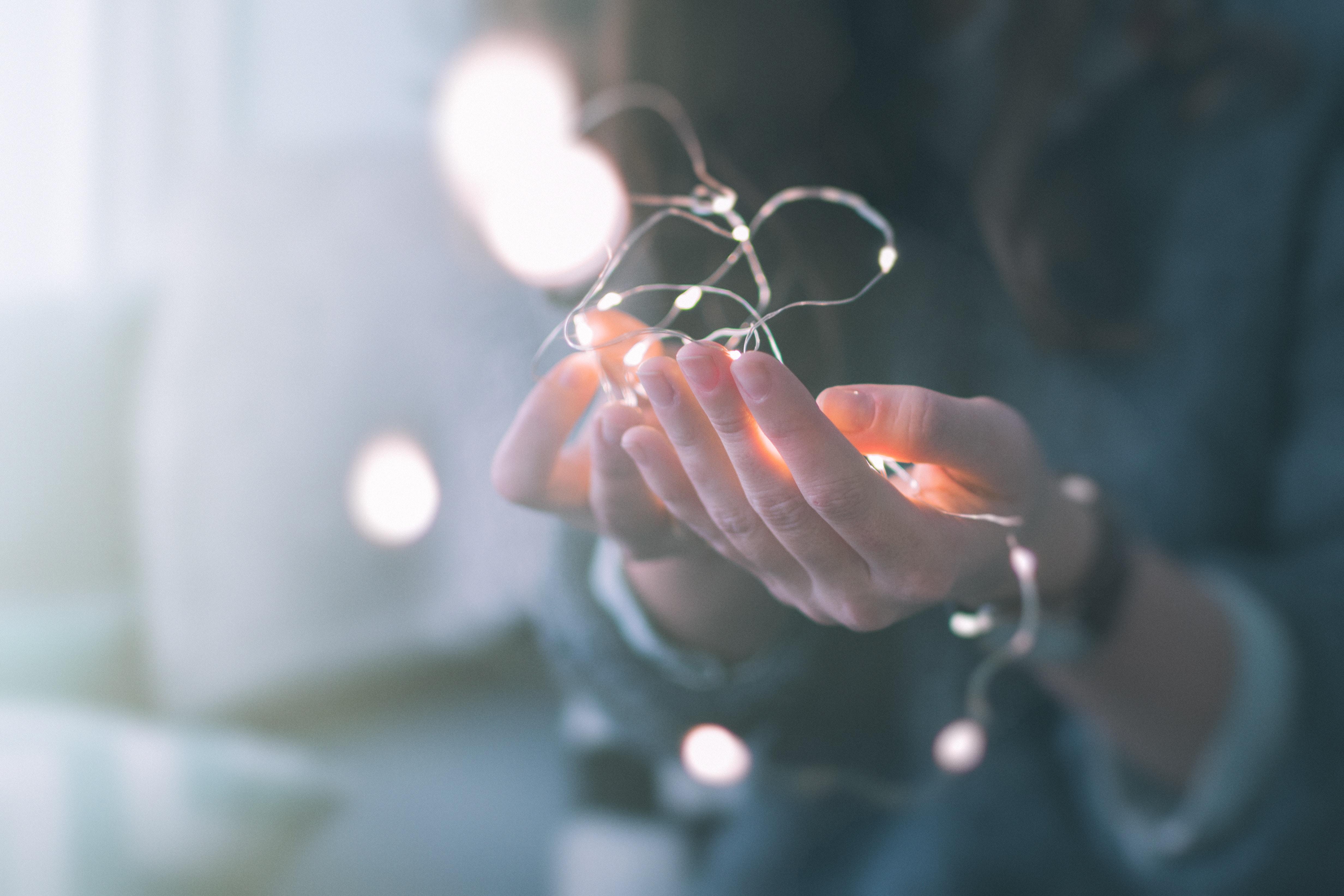 Des mains qui tiennent de petites lumières blanches